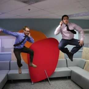 photo of two men jumping in the air while on the phone